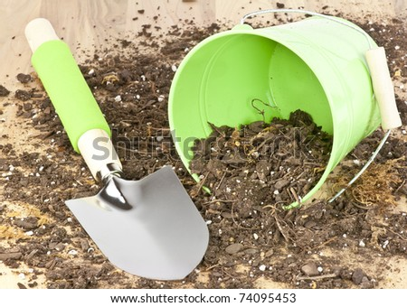 A spade ,soil and bucket representing gardening