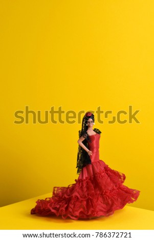 a spanish doll dressed as a flamenco dancer, with the characteristic traje de flamenca, the typical dot-patterned dress, in a yellow background with a blank space on top