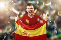 A Spanish fan, a fan of a man holding the Spanish national flag in his hands. Soccer fan in the stadium.