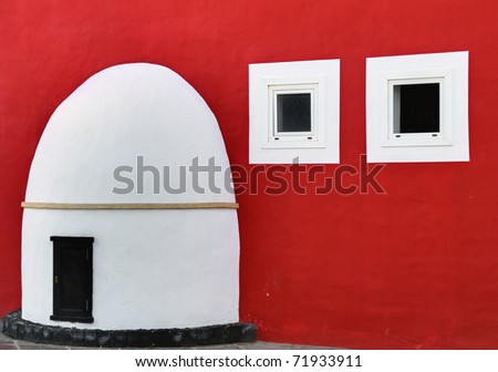 A Spanish porch, door, and two windows on a richly coloured red wall