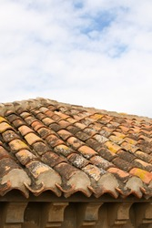 A Spanish-style roof made out of terracotta coloured tiles under a cloudy sky in Malaga, Spain.  Image has copy space.