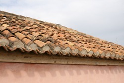 A Spanish-style roof made out of terracotta coloured tiles under a grey, cloudy sky in Malaga, Spain.  Image has copy space.