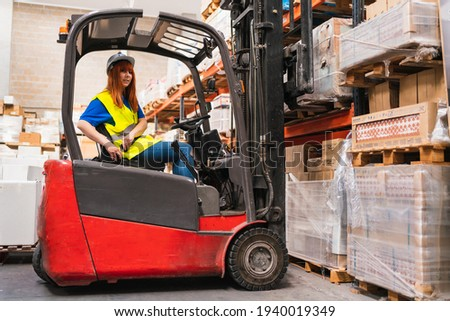 A Spanish worker putting on a forklift seat belt while picking up a pallet in a warehouse Foto stock ©