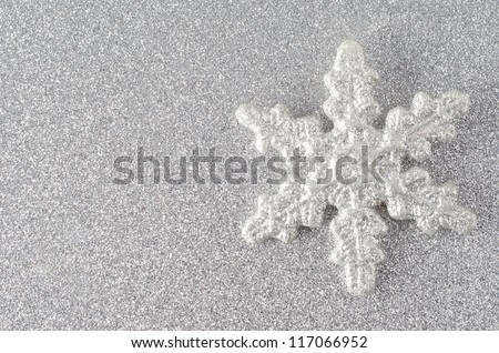 A sparkly silvery glitter encrusted snowflake on a silver glitter background.  Copy space to left.