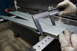 A specialist at the factory measures the accuracy of bending of  metal sheet used as a cover for an industrial radiator of a convector type with vernier caliper, quality control on a production line