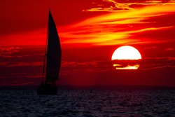 A spectacular sunset over Chesapeake Bay Maryland as captured from the east shore. Image features the large sun going down among clouds on a red sky and the silhouette of a sailboat with full sails.