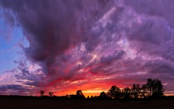 A spectacular, vivid stormy sky at sunset in the American Midwest (Indiana). Photographed just after the sun dipped below the horizon and after as storm clouds were dissipating.