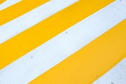 a speed bump that intersects yellow and white on the road