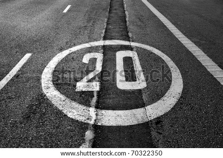 a speed limit sign painted on the road - stock photo