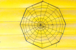 A spiderweb against the wall of a yellow painted log cabin creates an interesting abstract composition.