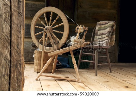 A spinning wheel with yarn baskets and old chair on a log cabin porch.