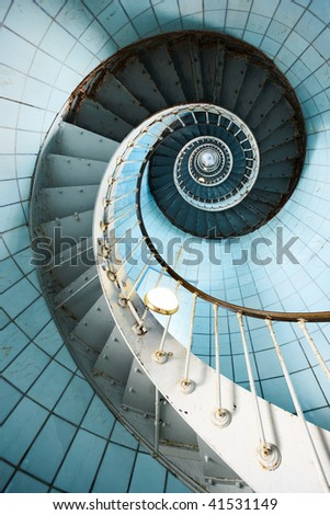 A spiral staircase going up with blue tiled wall (Charente Maritime / France) - stock photo