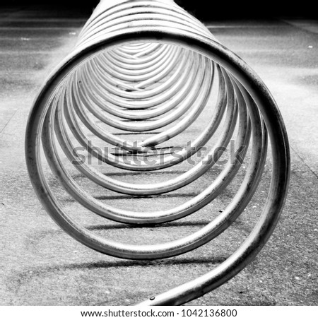 A spiraling piece of curved metal pipe acts as a bike corral on a city street at night.