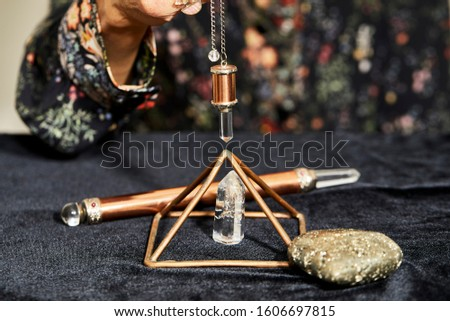A spiritual healer using a crystal pendulum over another quartz crystal in a pyramid