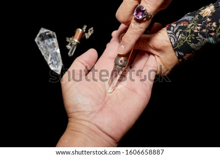 A spiritual healer using a crystal wand on a man's hand