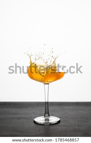 A splash of an orange cocktail in a coupe glass Photo stock ©