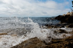 A splash of seawater on a rocky shore at daytime