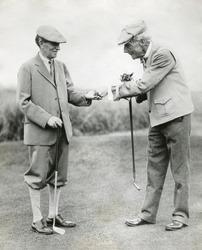 A splendid long putt deserves a dime'. John D. Rockefeller hands Harvey Firestone a dime during a golf match at Orvond Beach, Florida. Jan. 31, 1930.