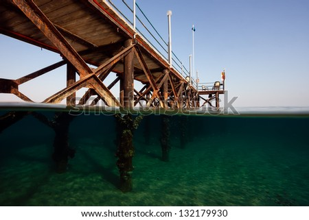 A split shot of a hotel jetty leading into a tropical sea