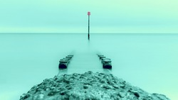 A split toned long exposure image of a groyne and a groyne marker, foreground defocussed image