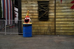 A spooky clown head sits on top of a trashcan