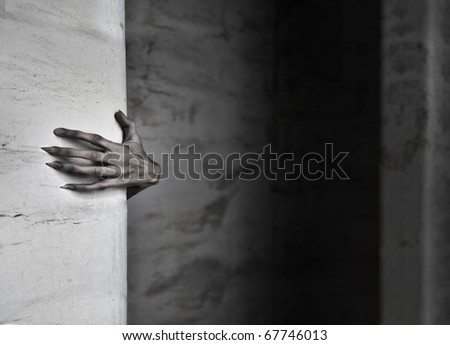 A spooky female hand protruding from behind a wall