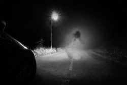 A spooky ghost of a woman in the road below a single street light in the countryside. Lit up by car headlights at night. With a grunge, vintage, old edit