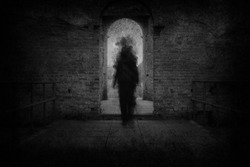 A spooky ghost, walking towards the camera, framed by the archway of an old building. With a grunge, vintage, blurred edit.