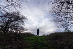 A spooky, hooded figure standing on a country path between trees on a winters day