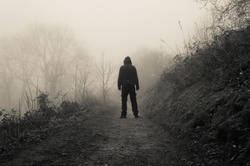 A spooky hooded figure standing on a country path on a eerie foggy winters day