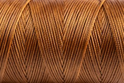 A spool of brown thread in close-up. Waxed brown sewing thread for leather products. Brown thread.