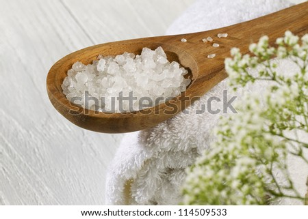 A spoon of spa salt and a white towel on a wooden background