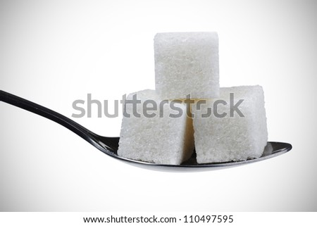 a spoonful of sugar cubes.isolated on white