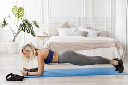 A sportive attractive woman doing yoga, stands on bent arms in a plank pose, a sportive girl trains at home. Healthy lifestyle concept.