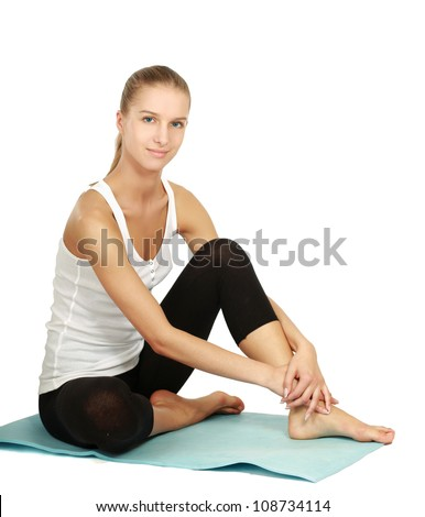 A sportive young girl sitting on the floor, isolated on white background