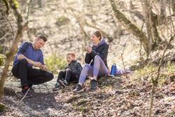 a sports family of tourists a man, a woman and a child sit resting in the forest on a hike, a mother drinks tea a child, a father whittles a staff from a stick with a knife, and the child is surprised