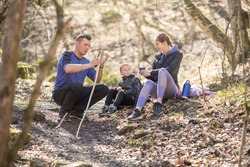 a sports family of tourists a man, a woman and a child sit resting in the forest on a hike, mom drinks tea, dad whittles a stick with a knife