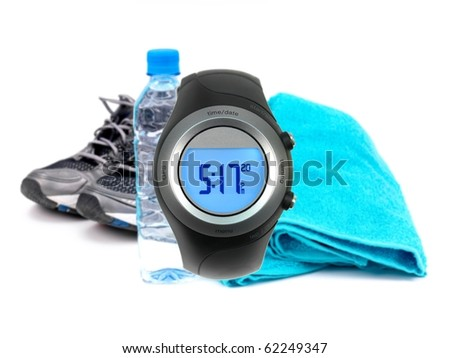 A sports watch isolated against a bottle of water, joggers and a sports towel