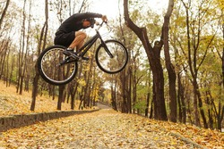 A sportsman performing a jump on trial bike in the woods. Horizontal outdoors shot.