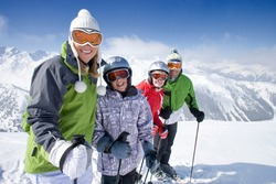 A sporty family of skiers standing in row together on top of the mountain while smiling at the camera as they get ready adventure trip