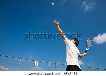 A sporty young asian male playing tennis