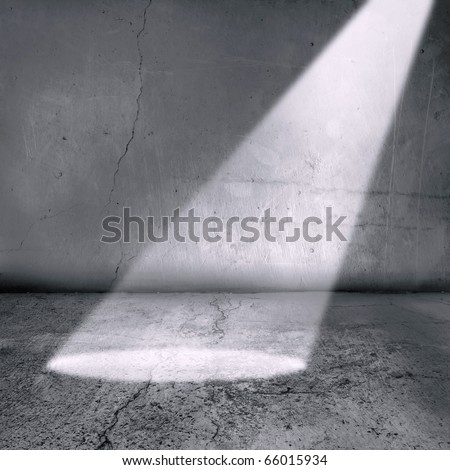 A spotlight shines into what could be a prison cell or generally an old grunge textured room and walls.