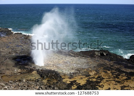 "A ""spouting horn"" is created by Pacific Ocean wave action along the volcanic rock coast of Kauai, Hawaii."