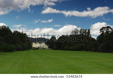 A sprawling lawn leads to a Georgian Revival Mansion that is the Australian Governor General's Residence - Government House, Canberra.