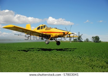 A spray plane flies low over a field.