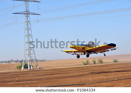 A spray plane or crop duster flies dangerously underneath electricity power lines while applying chemicals to a field of crops.