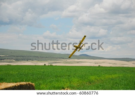 A spray plane pulls up and banks over an alfalfa field.
