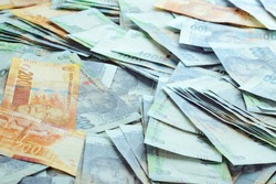 A spread of one hundred Rand notes and two hundred Rand notes cash South African Rands ZAR spread out on a textured table filling the frame