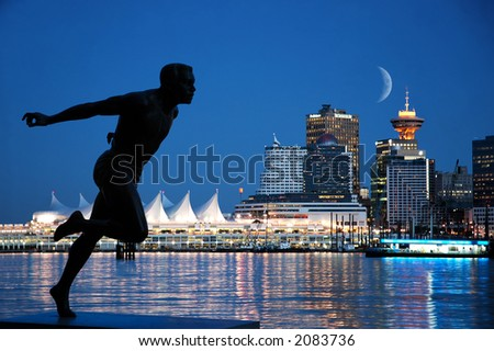 A sprinter's statue in Stanley Park with background of Canada Place, Vancouver, B.C.