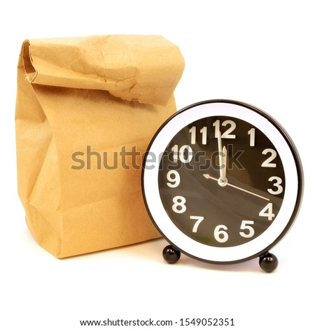 A square format isolated over white image of a brown paper bag and clock with details of noon hour to illustrate packing a homemade lunch for school or work. #1549052351